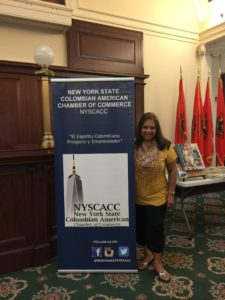 foto Con el Poster de la Cámara Colombo Americana del Estado de New York